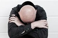 Mann stützt Kopf in Arme